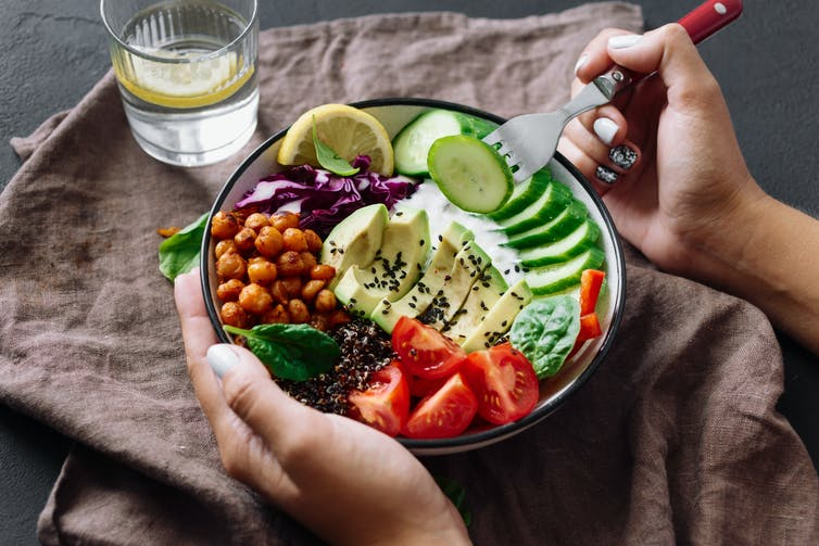 A bowl of healthy foods, including avocado, chickeas, and tomatoes.