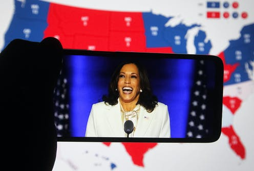 Photo of Harris on a cell phone in front of an electoral map