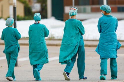 Cuatro sanitarios con su vestimenta de trabajo de espaldas caminando.