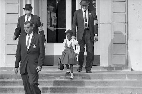Men in suits escort a little girl in a dress outside of a building in an old photo..