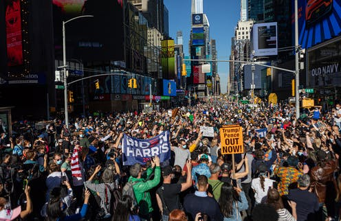 Crowds holding pro-Biden and anti-Trump signs in Times Square