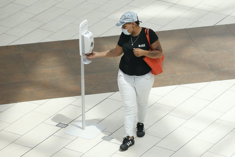 A woman wearing a mask using a hand sanitizer dispenser.