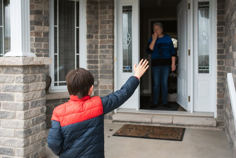 A young boy waves to his grandmother at the door of a home.