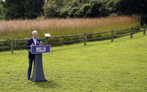 Biden stands in front of a podium with a wheat field behind him.