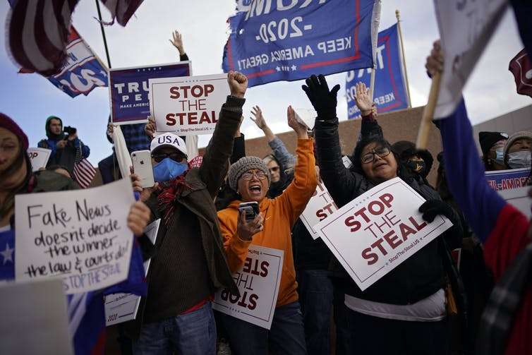 Trump supporters holding signs saying 'stop the steal' while protesting the election result