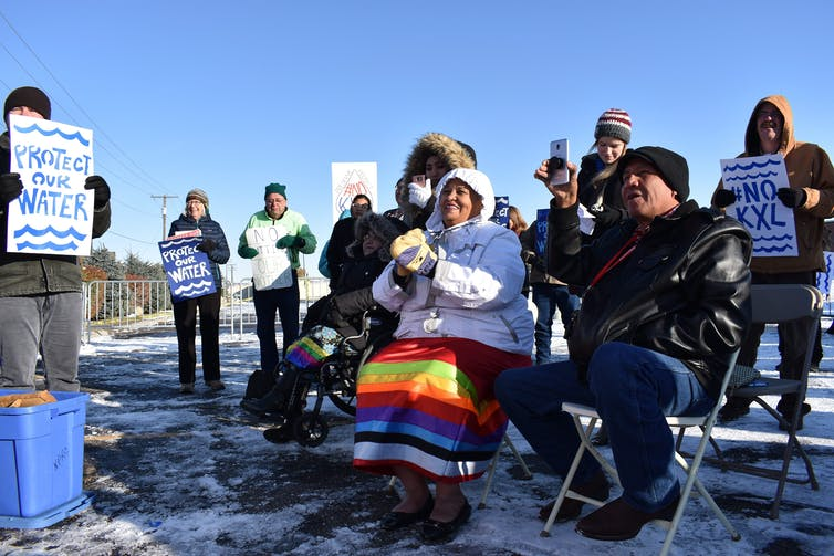 People hold signs against the Keystone XL pipeline.