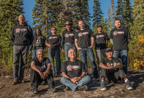 A group of 10 men — three sitting on the ground and seven standing behind them — wearing DUDES Club shirts outdoors in front of large evergreen trees.