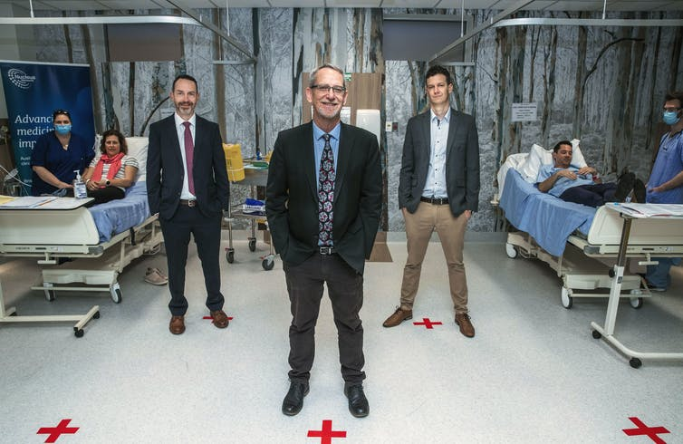 Researchers standing in a room with patients and nurses.