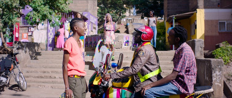 An urban street scene where two men on a stationary motorbike chat to a young woman standing in front of them and another young woman with pink hair extensions comes down some stairs towards them in the background.