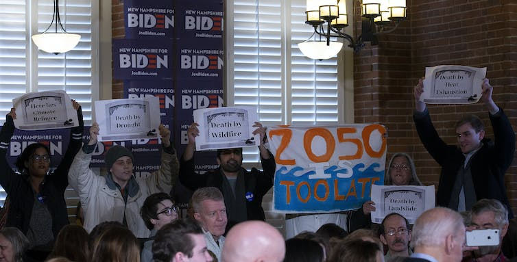 Protesters hold signs warning about climate change at a Democratic Primary event for Joe Biden's campaign.