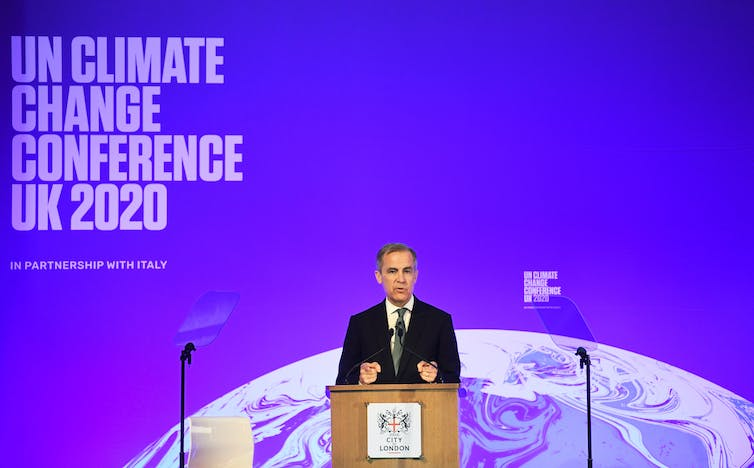 Governor of the Bank of England Mark Carney stands before a lectern at an event launching COP26.