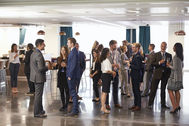 People stand networking at a conference