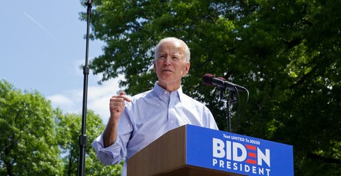 Joe Biden delivers a speech at a podium outside.