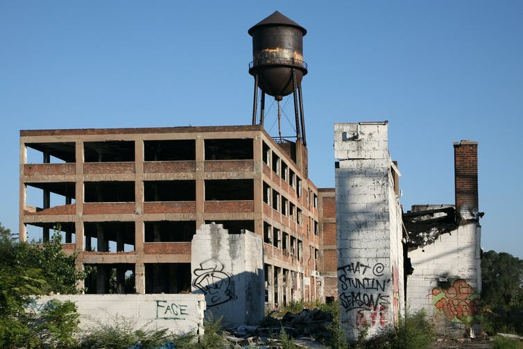 An abandoned factory sits amid overgrown vegetation, with a rusted water tower behind it.