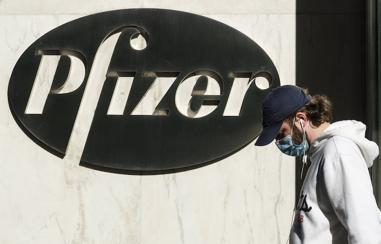 Man wearing a face mask walks past Pfizer sign on building.