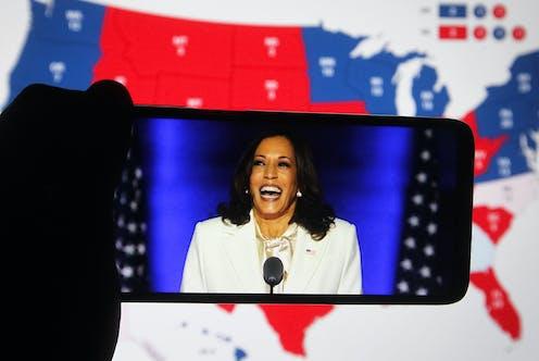 Kamala Harris vue sur un smartphone, sur fond de carte électorale des États-Unis