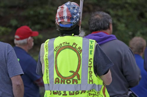 A group of people face away from the camera. A man in the foreground wears a Stars & Stripes cap and a florescent safety vest with writing supporting the Qanon conspiracy theory in hand lettering.