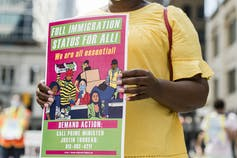 A woman carries a sign during a protest for migrant worker rights. The sign reads: full immigration status for all.