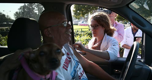 A man gets a flu shot at a drive-through clinic.