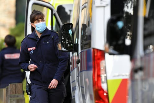 A paramedic wearing a mask next to an ambulance
