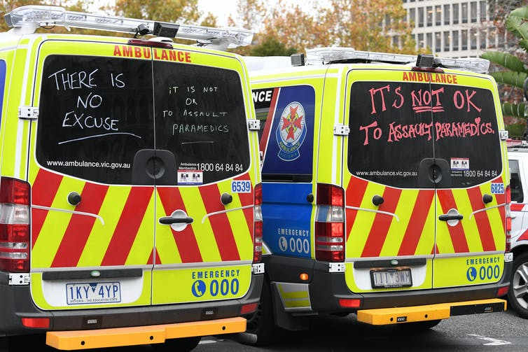 Two ambulances featuring written messages about how it's never OK to assault paramedics