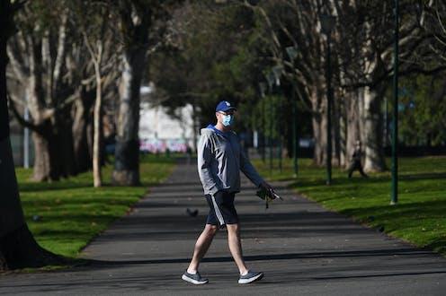 A mean wearing a mask walks through a park.