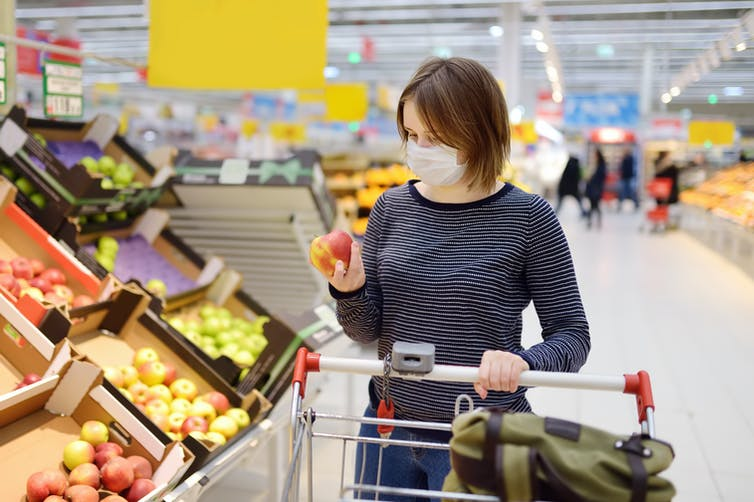 A woman wears a mask in the supermarket.