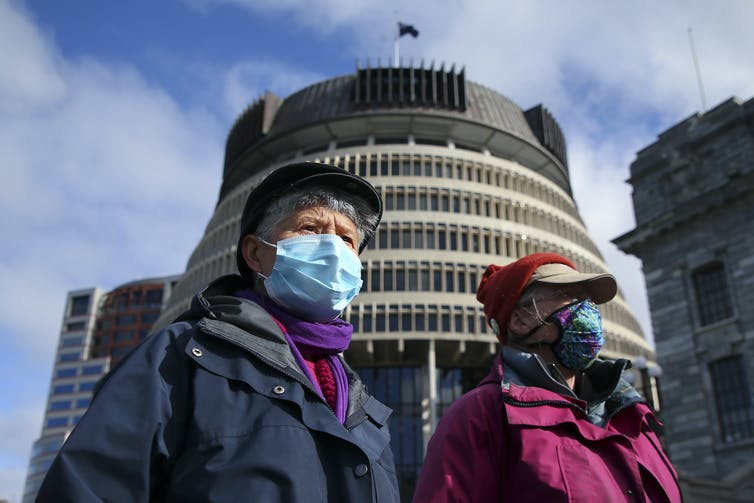 Two women wearing masks outside New Zealand's parliament building in Wellington.