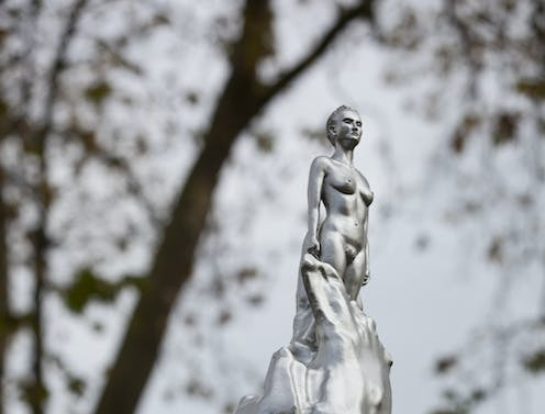 staute of a silver lady emerging from a silver flurry.