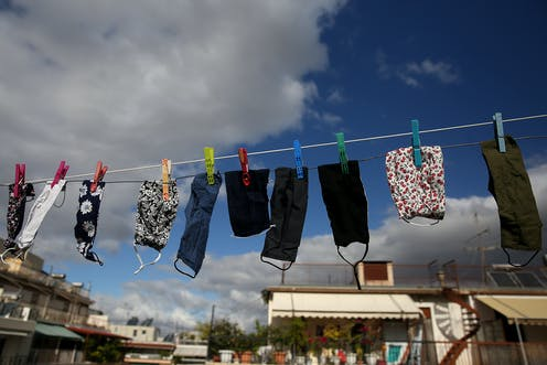 Face masks hanging up to dry on a washing line.