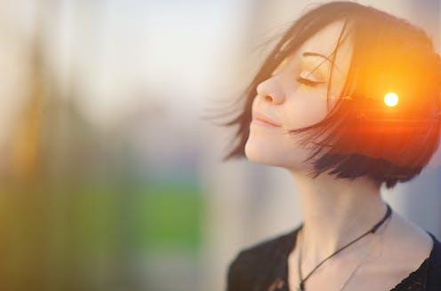 Mujer con el rostro feliz y ojos cerrados y una puesta de sol reflejada en el lateral de su cabeza.