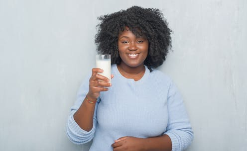 Woman holding up a glass of milk