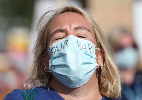 WOman wearing face mask demanding fair pay.