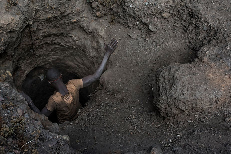 A man, seen from above, getting into a hole in the ground