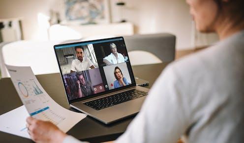 Una persona con documentación en la mano conversa a través del ordenador con otras cuatro.