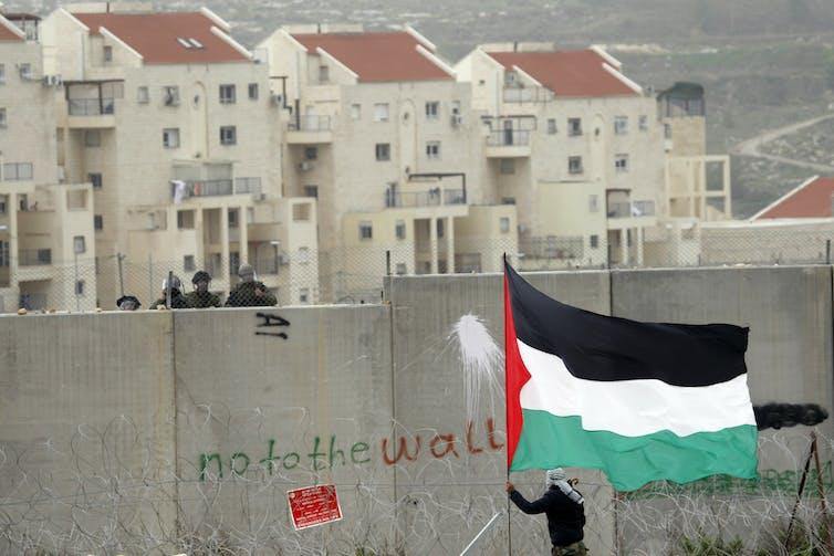 Un homme agite un drapeau palestinien devant un mur avec des graffitis qui se lit comme suit: Non au mur.  Des soldats israéliens peuvent être vus derrière le mur.