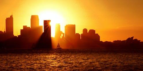 A hot sun setting over a Sydney skyline.