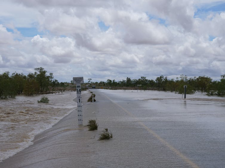 A flooded road in the Northern Territory with a flood marker.