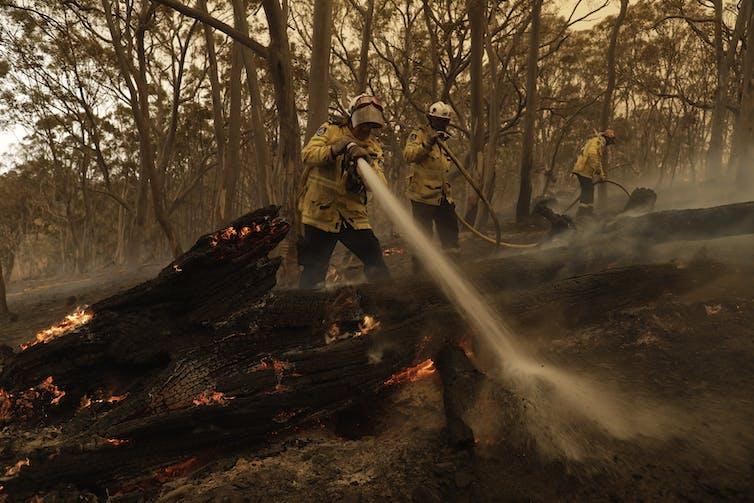 A firefighter hosing down spot fires.
