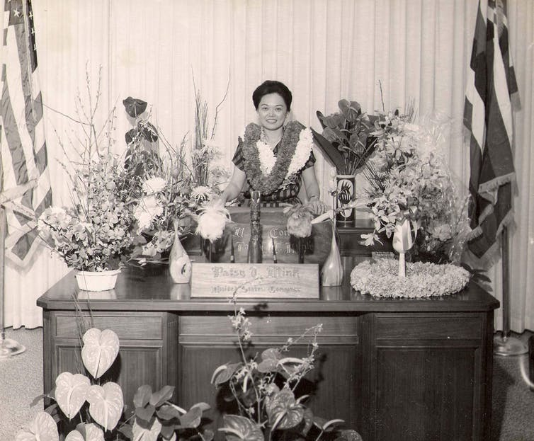 Black and white image of Mink wearing a lei and surrounded by flowers