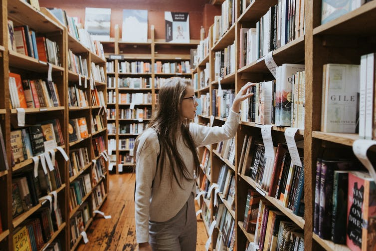 Girl walks through bookshop.
