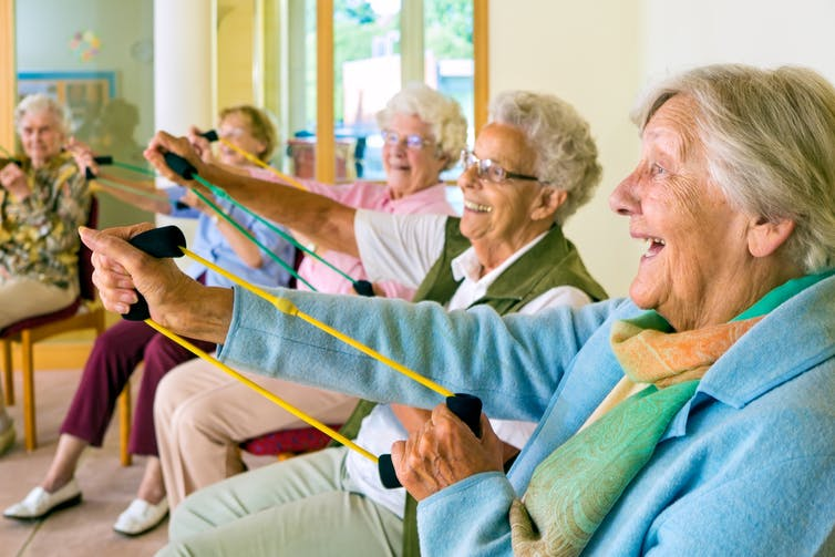 Elderly people in a nursing home doing group exercise sitting down