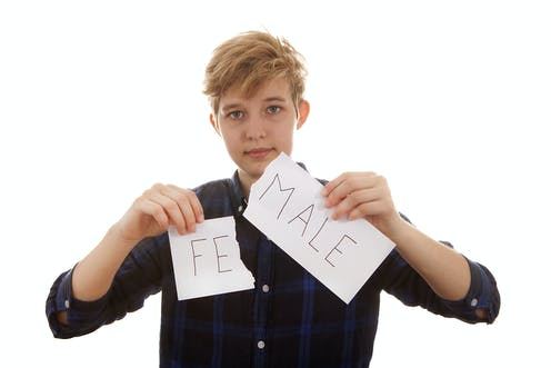 Young trans person tears up paper into two pieces bearing letters 'FE' and 'MALE',