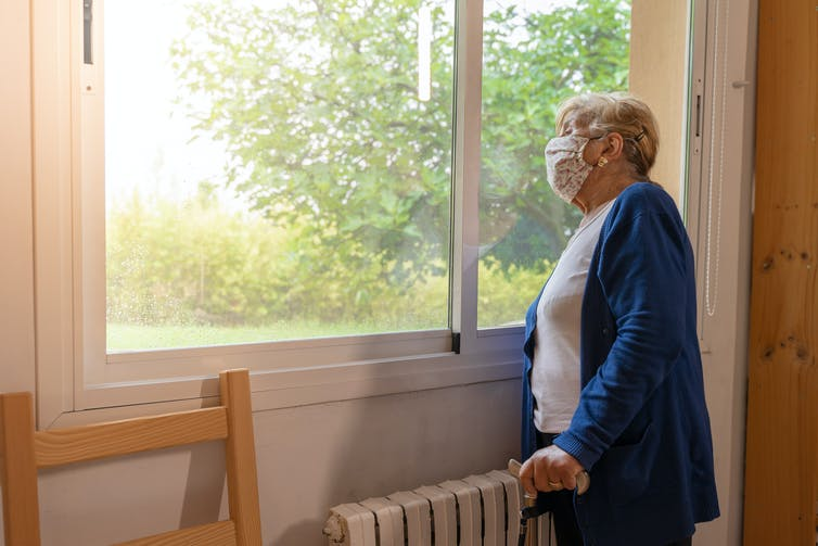An elderly woman wearing a mask looks out the window.