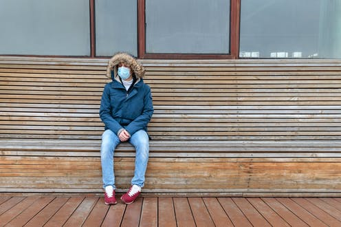 Una persona con mascarilla y abrigo sentada en un banco,