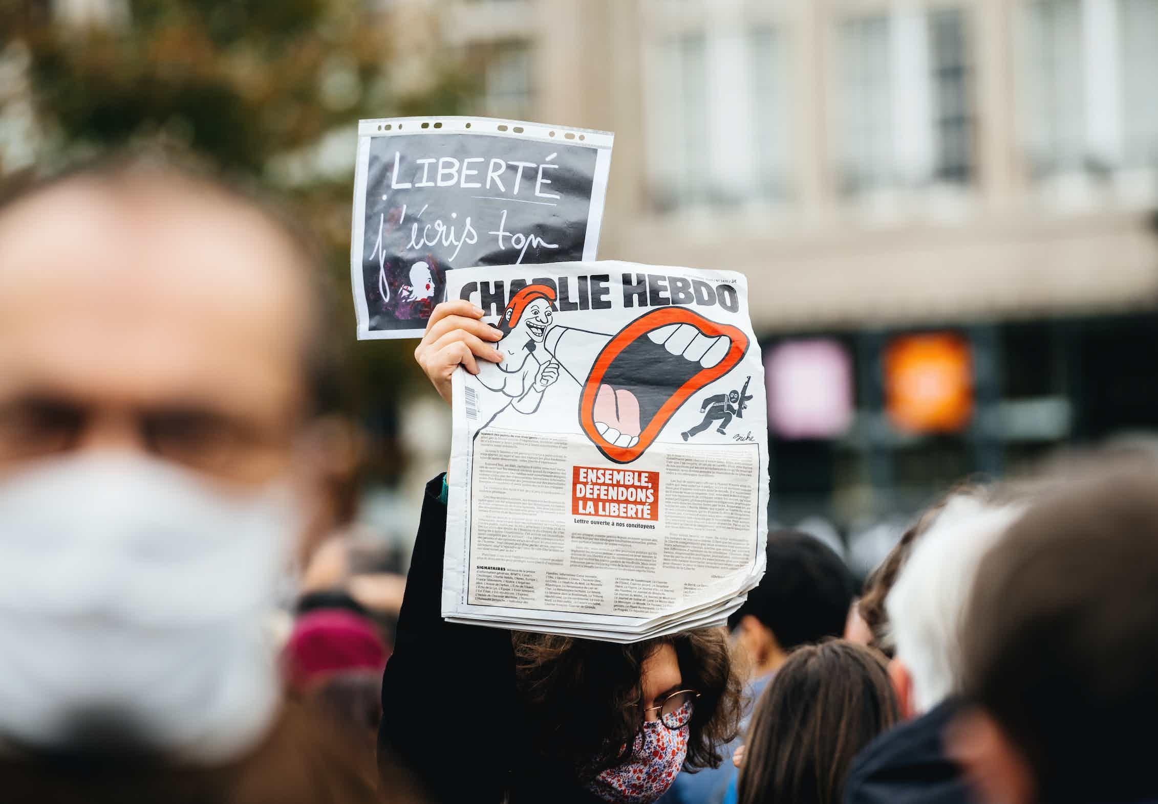 Una mujer con el periódico Charlie Hebdo rinde homenaje al profesor de historia Samuel Paty, decapitado el 16 de octubre de 2020 tras mostrar caricaturas del profeta Mahoma en clase. (Estrasburgo, Francia - 19 de octubre de 2020).Shutterstock / Hadrian