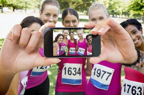 Mujeres con ropa deportiva rosa participantes en una carrera contra el cancer de mama se hacen una fotografía con un móvil.