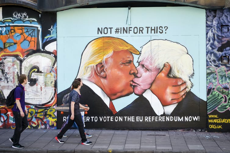 Graffiti depicting Donald Trump and Boris Johnson kissing, in the style of the famous mural 'My God, Help Me to Survive This Fatal Attraction', painted on the Berlin Wall.