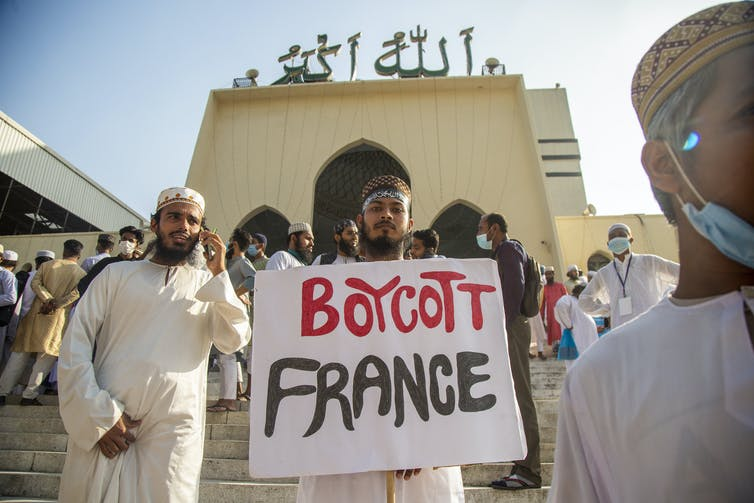 A young man holds up a sign reading 'boycott France'