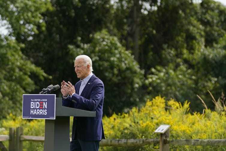 Joe Biden speaking at a lectern outside in front of a stand of trees.